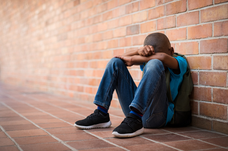 Photo for Young boy sitting alone with sad feeling at school. Depressed african child abandoned in a corridor and leaning against brick wall. Bullying, discrimination and racism concept at school with copy space. - Royalty Free Image