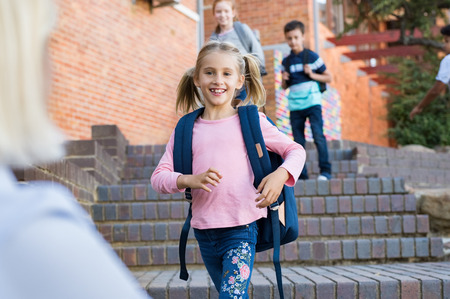 Photo pour Happy cute girl running with stretched arms towards mother after school. Young school child feeling happy after lesson at primary school. Elementary student kids running into mother's hands to hug her after school. - image libre de droit