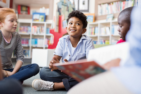 Foto de Multiethnic group of kids sitting on floor in circle around the teacher and listening a story. Discussion group of multiethnic children in library talking to woman. Portrait of smiling hispanic boy in elementary school. - Imagen libre de derechos