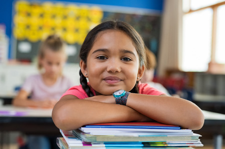Foto de Portrait of cute little schoolgirl leaning on stacked books in classroom. Happy young latin girl in casual keeping chin on notebooks. Closeup face of smiling girl at elementary school.  - Imagen libre de derechos