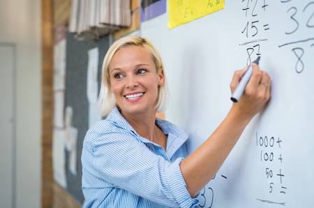 Foto de Teacher teaching how to count on whiteboard in classroom. Smiling blonde woman explaining additions in column in class. Math's teacher explaining arithmetic sums to elementary children. - Imagen libre de derechos