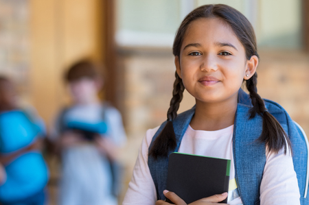 Foto de Smiling student girl wearing school backpack and holding exercise book. Portrait of happy asian young girl outside the primary school. Closeup face of smiling hispanic schoolgirl looking at camera. - Imagen libre de derechos