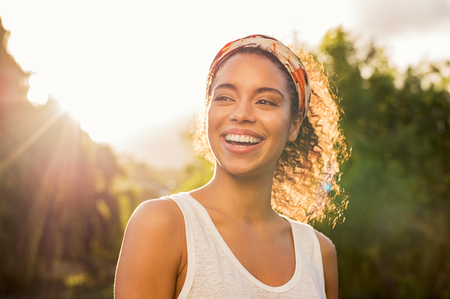 Photo for Portrait of beautiful african american woman smiling and looking away at park during sunset. Outdoor portrait of a smiling black girl. Happy cheerful girl laughing at park with colored hair band. - Royalty Free Image