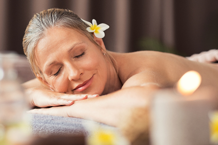 Foto de Beautiful blond woman relaxing at spa after body massage. Portrait of mature woman lying on massage table with closed eyes. Senior woman lying on a lounger at wellness center with candles. - Imagen libre de derechos