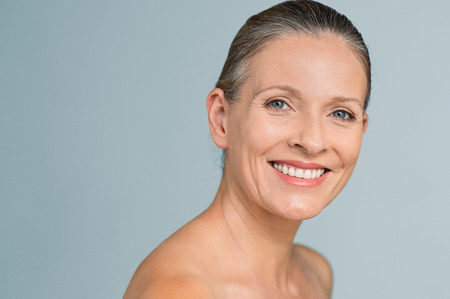 Foto de Portrait of a smiling senior woman looking at camera. Closeup face of mature woman after spa treatment isolated over grey background. Anti-aging concept. - Imagen libre de derechos