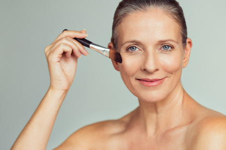 Photo pour Closeup portrait of mature woman applying tonal foundation on face with makeup brush. Smiling senior woman applying powder for make up. Cosmetics and make-up portrait. - image libre de droit