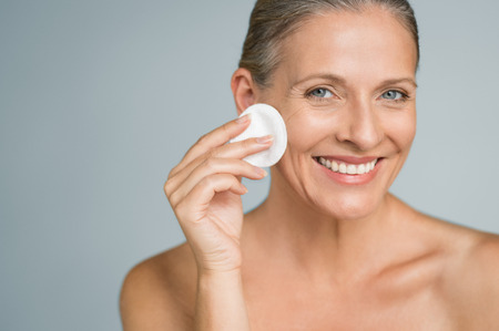 Foto de Healthy mature woman removing makeup from her face with cotton pad isolated on grey background. Beauty portrait of happy woman cleaning skin and looking at camera. - Imagen libre de derechos