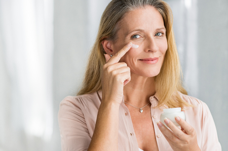 Photo pour Smiling senior woman applying anti-aging lotion to remove dark circles under eyes. Happy mature woman using cosmetic cream to hide wrinkles below eyes. Lady using day moisturizer to counteract the aging of the skin. - image libre de droit