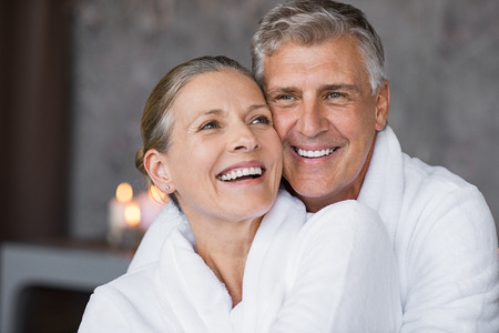 Photo for Smiling husband embracing cheerful wife from behind at spa. Laughing mature couple enjoying a romantic hug at wellness center after massage. Senior man and woman in white in bathrobe relaxing at spa. - Royalty Free Image