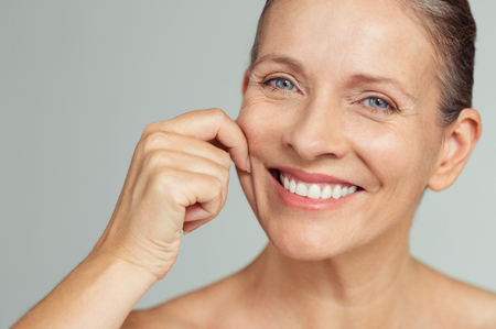 Foto de Senior woman pulling cheeks to feel softness and looking at camera. Beauty portrait of happy mature woman smiling with hands on cheek isolated over grey background. Aging process and perfect skin concept. - Imagen libre de derechos