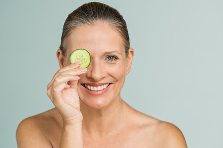 Photo pour Portrait of smiling senior woman covering an eye with a cucumber slice isolated on grey background. Beauty mature woman holding slice of cucumber and looking at camera. Skincare and facial treatment. - image libre de droit