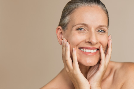 Foto de Beauty portrait of mature woman smiling with hand on face. Closeup face of happy senior woman feeling fresh after anti-aging treatment. Smiling beauty looking at camera while touching her perfect skin. - Imagen libre de derechos
