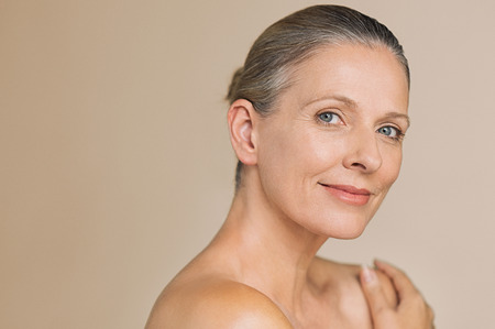Photo pour Smiling senior woman with bun hair and hand on naked shoulder. Portrait of beauty mature woman isolated over grey background with copy space looking at camera. Body and skin care concept. - image libre de droit