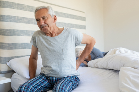 Foto de Senior man suffering from back pain at home while wife sleeping on bed. Old man with backache having difficulty in getting up from bed. Suffering from backache and sitting on bed in the morning. - Imagen libre de derechos