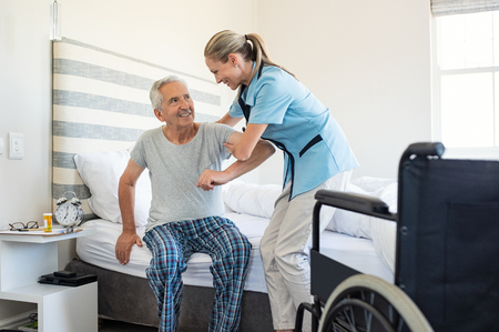 Foto de Smiling nurse assisting senior man to get up from bed. Caring nurse supporting patient while getting up from bed and move towards wheelchair at home. Helping elderly disabled man standing up in his bedroom. - Imagen libre de derechos