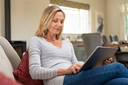 Photo pour Beautiful mature woman sitting on couch and using digital tablet. Smiling lady browsing internet over tablet at home. Middle age woman holding computer at home. - image libre de droit