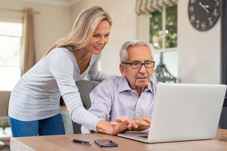 Photo pour Senior man and mature daughter smiling and looking at laptop at home. Happy daughter teaching and showing new computer technology to her old dfather. Old man learn to use computer. - image libre de droit