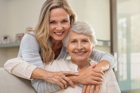 Foto de Cheerful mature woman embracing senior mother at home and looking at camera. Portrait of elderly mother and middle aged daughter smiling together. Happy daughter embracing from behind elderly mom sitting on sofa. - Imagen libre de derechos