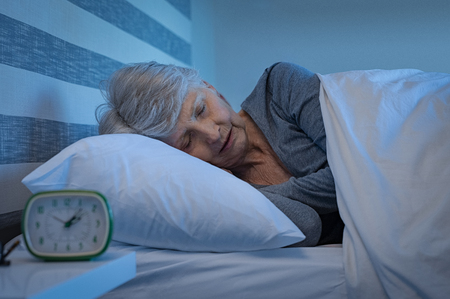 Foto de Old woman in grey hair sleeping peacefully at night time in bed. Senior woman lying on side and sleeping at home. Mature woman feeling relaxed at home while sleeping at night. - Imagen libre de derechos