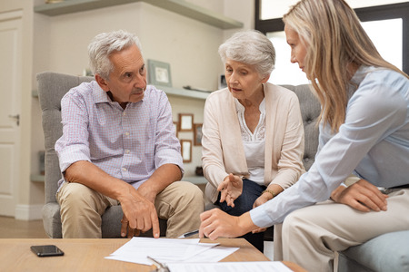 Foto de Business agent planning with a retired couple their future investment opportunities. Financial advisor talking to elderly man and woman and pointing the terms of contract on document. Retirement plans and terms. - Imagen libre de derechos