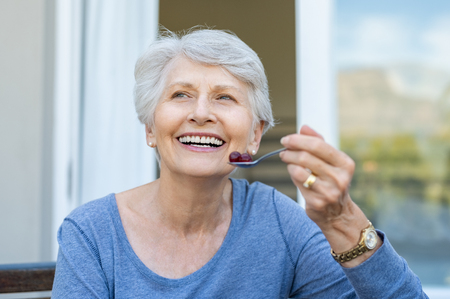 Photo pour Cheerful senior woman holding red grapes in spoon and make a beautiful white smile. Smiling old woman looking away while eating fresh fruits for breakfast. Mature woman enjoying old age and healthy eating. - image libre de droit