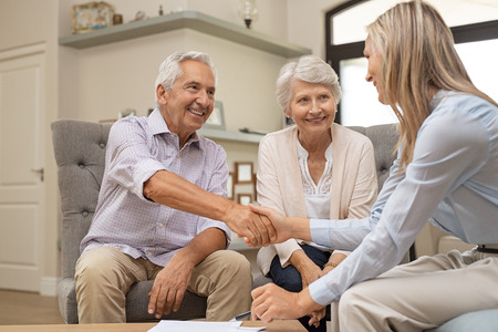 Foto de Happy senior couple sealing with handshake a contract for the retirement. Smiling satisfied retired man making sale purchase deal concluding with a handshake. Elderly man and woman smiling while agree with financial advisor. - Imagen libre de derechos