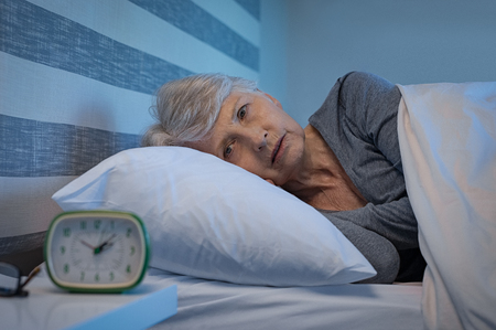 Photo pour Worried senior woman in bed at night suffering from insomnia. Old woman lying in bed with open eyes. Mature woman unable to sleep at home. - image libre de droit