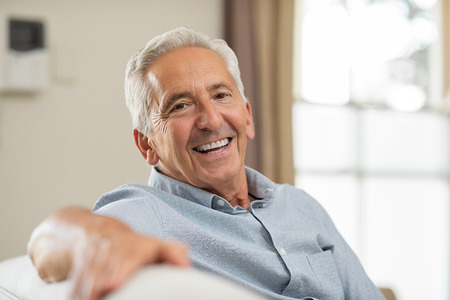 Foto de Portrait of happy senior man smiling at home. Old man relaxing on sofa and looking at camera. Portrait of elderly man enjoying retirement. - Imagen libre de derechos