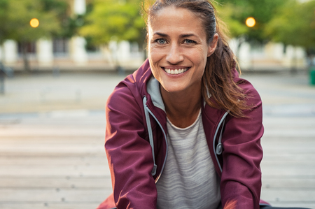 Photo for Portrait of smiling woman sitting on floor of city street after running. Healthy mature runner resting after workout exercise and looking at camera. Active latin sporty woman enjoying outdoors in autumn. - Royalty Free Image