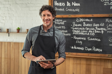 Photo for Mature waiter wearing black apron and standing in front of the blackboard with the menu of the day. Portrait of smiling man holding digital tablet and looking at camera. Happy small business owner working in cafeteria with digital tablet. - Royalty Free Image