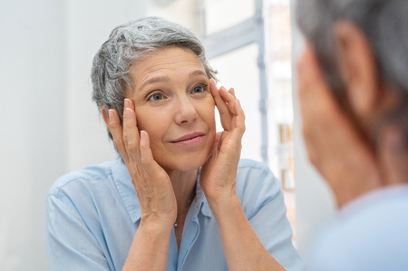 Photo pour Beautiful senior woman checking her face skin and looking for blemishes. - image libre de droit