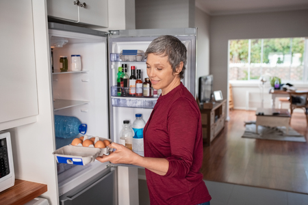 Photo for Senior woman removing eggs tray from refrigerator to prepare a pie. - Royalty Free Image