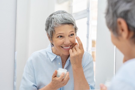 Photo pour Happy mature woman applying face lotion while looking herself in the bathroom mirror. Senior woman applying anti aging moisturizer on her face. Smiling lady holding little jar of skin cream and applying lotion during the morning routine. - image libre de droit