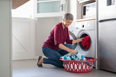 Foto per Happy senior woman loading dirty clothes in washing machine. Smiling mature woman sitting on floor putting clothed in washing machine from laundry basket. Housework. - Immagine Royalty Free