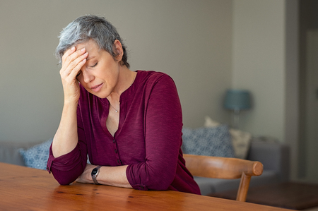 Photo for Senior woman suffering from headache while sitting at table in a living room. - Royalty Free Image