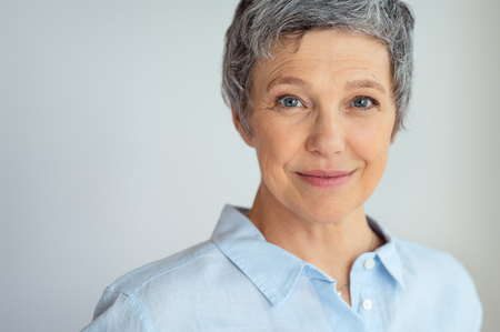 Photo for Closeup face of senior business woman standing against grey background with copy space. - Royalty Free Image