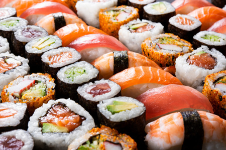 Foto de Overhead japanese sushi food. Maki ands rolls with tuna, salmon, shrimp, crab and avocado. Top view of assorted sushi, all you can eat menu. Rainbow sushi roll, uramaki, hosomaki and nigiri. - Imagen libre de derechos