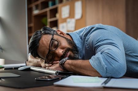 Photo for Tired multiethnic businessman sleeping in office. Middle eastern business man with eyeglasses worked late and fell asleep on the computer keyboard. Creative casual man sleeping at his working place - Royalty Free Image