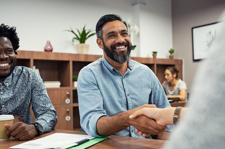 Photo pour Two business people shaking hands while sitting in meeting room. Middle eastern businessman shake hands to businesswoman. Portrait of happy smiling latin man signing off deal with an handshake. - image libre de droit