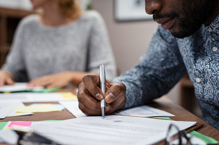 Photo pour Closeup of businessman hand signing on formal paper during a meeting in boardroom. African american business man signing a contract. Closeup of a businessperson sign contract and making a deal. - image libre de droit