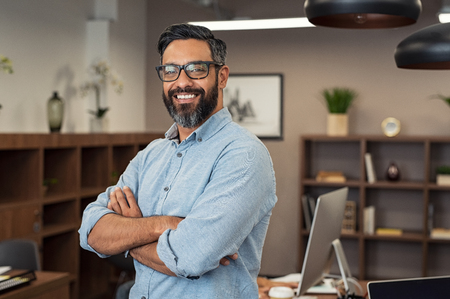 Photo pour Portrait of happy mature businessman wearing spectacles and looking at camera. Multiethnic satisfied man with beard and eyeglasses feeling confident at office. Successful middle eastern business man smiling in a creative office. - image libre de droit