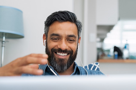 Photo pour Portrait of happy mature man making hand gestures while conversing with a video call at laptop with earphones. Cheerful casual businessman doing video calling at home. Middle eastern man relaxing at home while using digital tablet. - image libre de droit