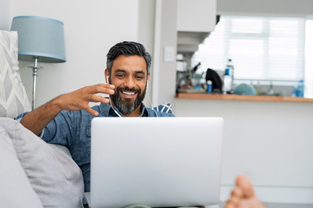 Foto de Happy mature man relaxing on couch while video calling using laptop at home. Latin man sitting on sofa and making a video call. Smiling middle eastern businessman doing online video chat while gesturing with hands. - Imagen libre de derechos