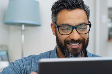 Foto de Relaxed mature man at home using digital tablet. Handsome hispanic man using laptop on sofa. Confident multiethnic guy with spectacles and beard using digital laptop. - Imagen libre de derechos