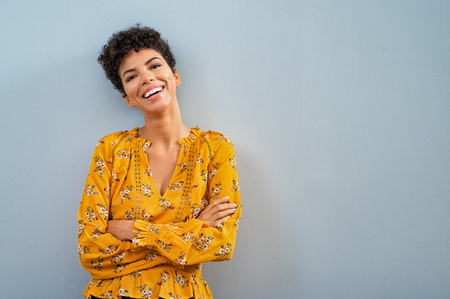 Foto de Portrait of beautiful cheerful girl smiling and looking at camera. Happy african woman in casual standing on blue background. Brazilian stylish woman with crossed arms and curly hair isolated with copy space. - Imagen libre de derechos