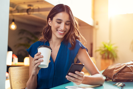 Foto de Young beautiful woman holding coffee paper cup and looking at smartphone while sitting at cafeteria. Happy university student using mobile phone. Businesswoman in casual clothes drinking coffee, smiling and using smartphone indoor. - Imagen libre de derechos