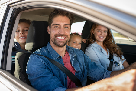Foto de Smiling young family with two children sitting in car and driving. Family relaxing during road trip while looking at camera. Portrait of happy father riding in a car with wife, son and daughter. - Imagen libre de derechos