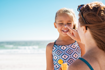 Foto de Young mother applying protective sunscreen on daughter nose at beach. Woman hand putting sun lotion on child face. Cute little girl with sunblock at seaside with copy space. - Imagen libre de derechos