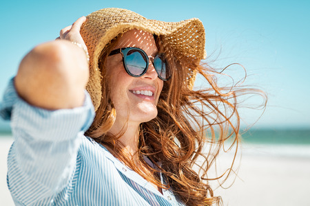 Foto de Side view of beautiful mature woman wearing sunglasses enjoying at beach. Young smiling woman on vacation looking away while enjoying sea breeze wearing straw hat. Closeup portrait of attractive girl relaxing at sea. - Imagen libre de derechos