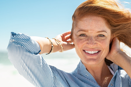 Foto de Portrait of beautiful mature woman with wind fluttering hair. Closeup face of healthy young woman with freckles relaxing at beach. Cheerful lady with red hair and blue blouse standing at seaside enjoying breeze looking at camera. - Imagen libre de derechos